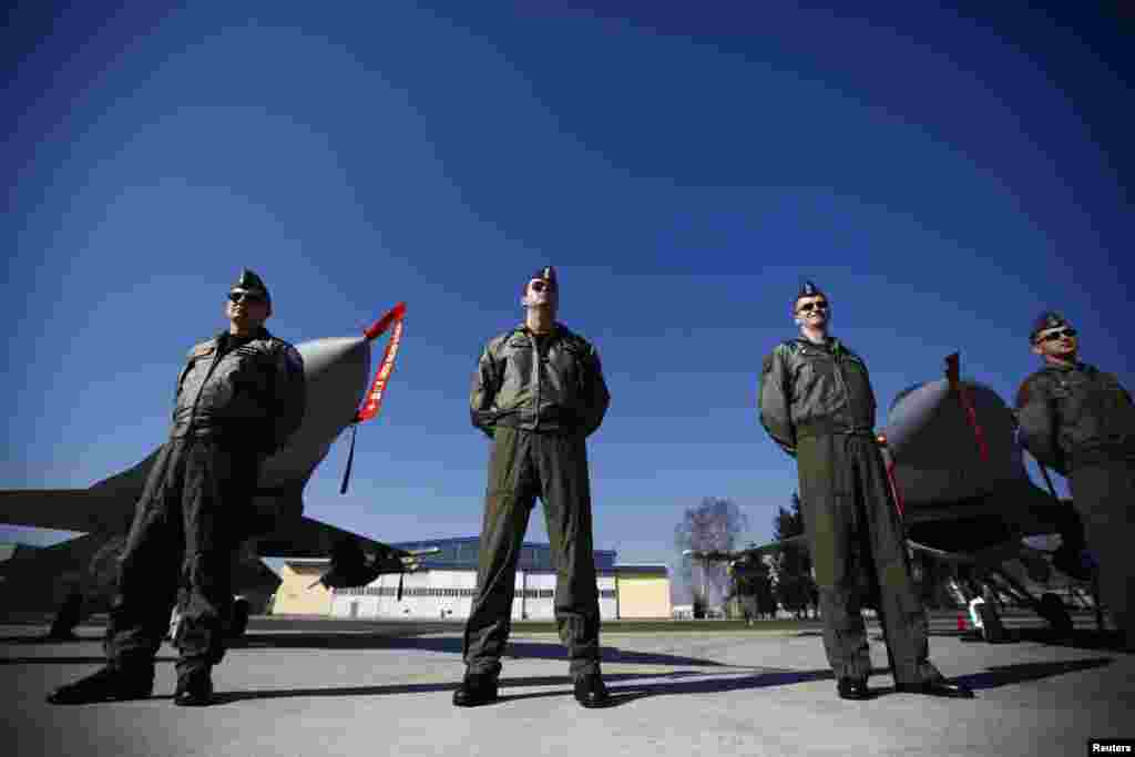 Polish pilots stand in front of F-16 fighter jets during a visit by the country's President Bronislaw Komorowski to the Lask airbase on March 11. (Reuters/Kacper Pempel)