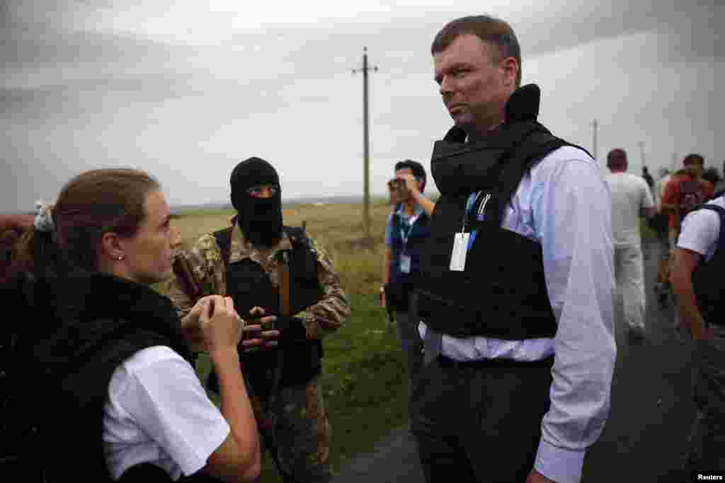 OSCE monitors speak with a pro-Russian separatist about gaining access to a crash site near Hrabove on July 18.