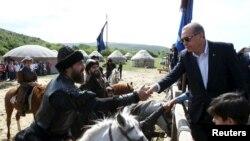 Президент Турции Реджеп Тайип Эрдоган пожимает руку актеру, задействованному на съемках турецкого сериала. Стамбул, 7 июня 2015 года.