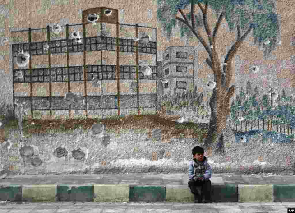 A Syrian child sits in front of a bullet-riddled mural on the wall of a former school in the rebel-held region of Eastern Ghouta, on the outskirts of the Syrian capital, Damascus. (AFP/Abdulmonam Eassa)