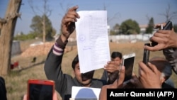 Journalists take images of the court verdict against the accused suspects outside the central jail in Haripur district on February 7, 2018.