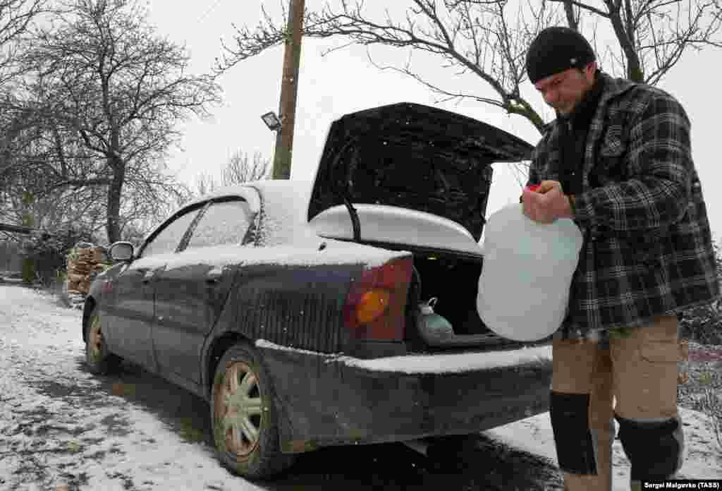 Мужчина выгружает бутыли с водой из багажника машины во дворе своего дома в Клиновке