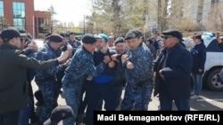 Астанада полиция арнайы жасағы наразылық митингісіне шыққандарды ұстап әкетіп барады. 10 мамыр 2018 жыл.