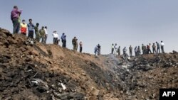 Iranians gather at the edge of a crater at the crash site of the Caspian Airlines plane, which fell into farmland near the city of Qazvin, northwest of Tehran.