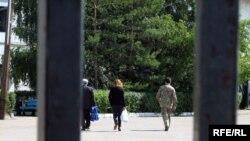 Джамиля Джакишева в сопровождении охранника идет в тюрьму КНБ, где сидит ее муж. Астана, 31 июля 2009 года.