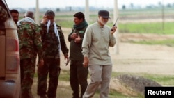 Iranian Revolutionary Guard Commander Qassem Soleimani (R) uses a walkie-talkie at the frontline during offensive operations against Islamic State militants in the town of Tal Ksaiba in Salahuddin province, March 8, 2015. File photo