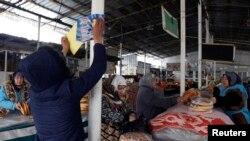 Кандидатқа дауыс беруге шақырған сайлау постерін базардағы тіреуге жапсырып жатқан партия белсендісі. Душанбе, 26 ақпан 2015 жыл.