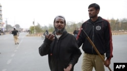 A Pakistan policeman, right, detains a cleric after a ceremony marking the death anniversary of provincial Governor Salman Taseer in Lahore on January 4.