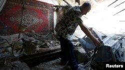 Чоловік серед уламків свого будинку, зруйнованого під час нещодавнього обстрілу, серпень, 2014 року