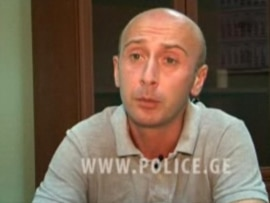 A handout photo taken from footage from the Georgian Interior Ministry's official website on July 9 shows Georgian presidential photographer Irakli Gedenidze answering investigators' questions.