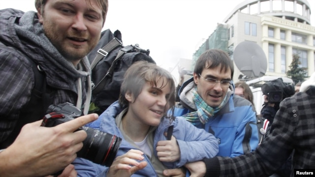 Freed Pussy Riot member Yekaterina Samutsevich (center) leaves the courtroom in Moscow on October 10.