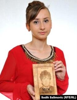 """Belma Malagić drži svoju knjigu """"Moć sudbine"""""""