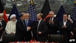 Afghan National Security Adviser Hanif Atmar (2R) and US Ambassador to Afghanistan James Cunningham (2L) hold their documents after signing a deal to allow some US troops to stay in Afghanistan in Kabul, September 30, 2014.