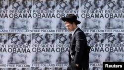 АҚШ билігін Джонатан Поллардты түрмеден босатуға шақырған плакаттар жанынан өтіп бара жатқан адам. Иерусалим, 20 наурыз 2013 жыл. (Көрнекі сурет)