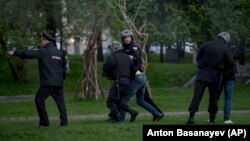 Russian police officers detain demonstrators protesting plans to construct a church in a park in Yekaterinburg.