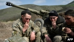 Nagorno-Karabakh -- Soldiers of the defense army of Nagorny Karabakh have lunch near a gun at their field position outside the village of Mataghis, some 70km north of Karabakh's capital Stepanakert, April 6, 2016