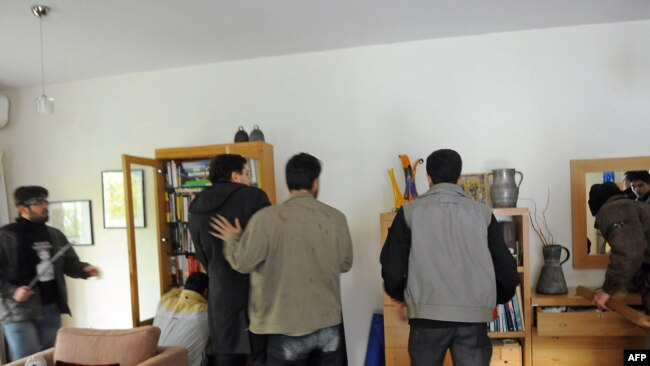 Protesters search an office at the British embassy in Tehran, 29Nov2011