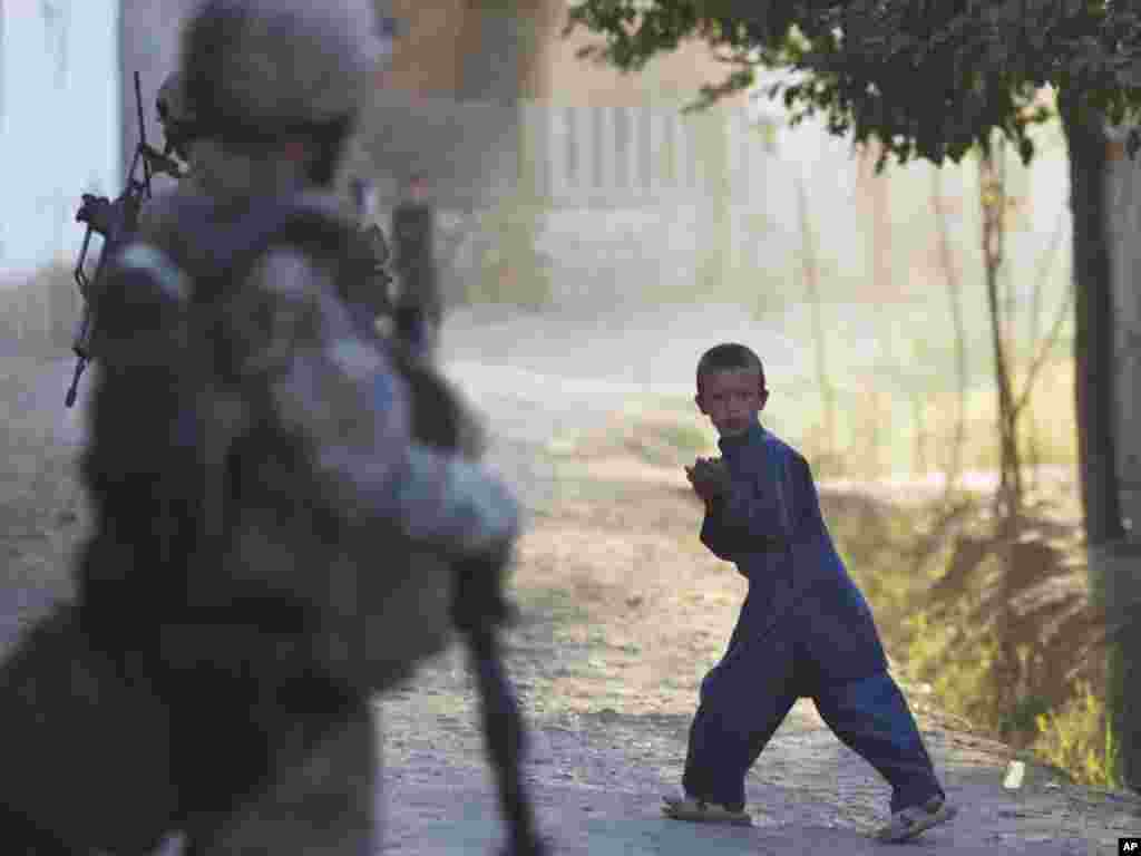 A young boy reacts as a German Army soldier patrols outside Kunduz, Afghanistan, on September 20. (Photo taken by Anja Niedringhaus for AP)