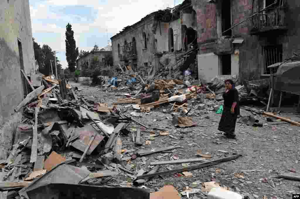 8 августа Россия начала трехдневную бомбардировку грузинского города Гори. На фото женщина проходит мимо разбомбленных домов в Гори. 9 августа 2008 года.