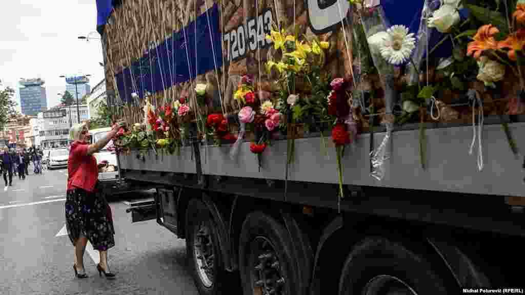 Një grua vë lule në kamionin që bart mbetjet e viktimave.