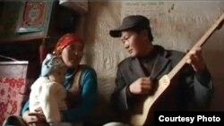 Тарбагатайлык жаш үй бүлө ыр ырдап, чер жазууда. «Youku» сайтындагы видеотасмадан алынган сүрөт.