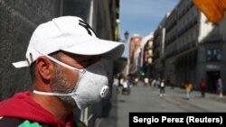 Un vânzător de bilete la loterie așteaptă cumpărători pe o stradă centrală din Madrid, altă dată foarte animată