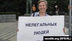"""Елена Рябинина вышла на одиночный пикет с плакатом с надписью: """"Нелегальных людей не бывает"""". Москва, август 2013 года."""