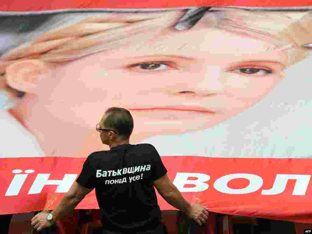 An opposition lawmaker stands next to a giant poster, featuring Yulia Tymoshenko in the Ukrainian parliament in Kyiv on September 6. (Photo by Sergei Supinsky for AFP)