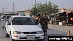 Сотрудники афганских сил безопасности досматривают автомобиль. Провинция Кундуз, 5 июля 2016 года.