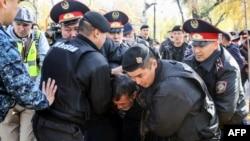 Полицейские задерживают мужчину на месте предполагаемой протестной акции в Алматы. 26 октября 2019 года.