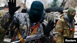 Вооруженный мужчина рядом со зданием захваченного пророссийскими силами отделения милиции. Славянск, 12 апреля 2014 года.