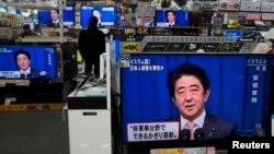 Жапония премьер-министрі Синдзо Абэнің баспасөз мәслихатын дүкенде теледидардан тікелей эфирде қарап тұрған адам. Токио, 20 қаңтар 2015 жыл. (Көрнекі сурет)