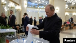 Президент России Владимир Путин опускает бюллетень в избирательную урну во время парламентских выборов. Москва, 18 сентября 2016 года.