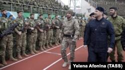 Шешенстан басшысы Рамзан Кадыров (оң жақтан екінші) қарулы жасақтың алдынан өтіп барады.