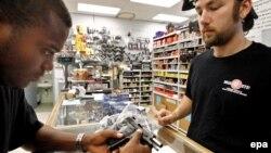 В оружейном магазине в штате Канзас продавец помогает покупателю с выбором. США, 26 июня 2008 года.