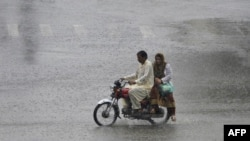 A Pakistani commuter drives his motorcycle through the monsoon rain in Lahore on July 24.
