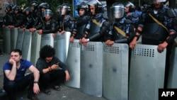 Демонстранти сидять на вулиці перед кордоном поліції в Єревані під час акції протесту у Єревані, 24 червня 2015 року