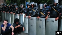 Armenia -- Demonstrators sit on a street in front of a line of riot police during a protest against an increase of electricity prices in Yerevan, June 24, 2015