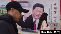 Қытайдың қазіргі басшысыСи Цзиньпиннің суреті бар көшедегі жарнаманың алдынан өтіп жатқан адамдар. Пекин, 26 ақпан 2018 жыл