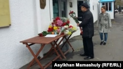 Мужчина возлагает цветы у консульства Франции. Алматы, 14 ноября 2015 года.