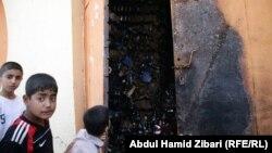 Ирак балалары бұрын ішімдік сатқан, қазір біреулер өртеп кеткен дүкенді тамашалап тұр. Ирбил, 8 мамыр 2012 жыл.