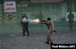 نیروی امنیتی عراق در حال شلیک گاز اشکآور بهسوی معترضان