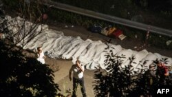 The bodies of victims of a bus crash are lined up on the road between Monteforte Irpino and Baiano on July 28