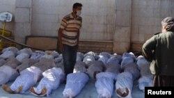 Оппозиция белсенділері химиялық қарудан мерт болды делінген адамдардың мәйіттерінің жанында тұр. Дамаскі, 21 тамыз 2013 жыл