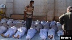 Активісти оглядають тіла людей, які, як вони кажуть, загинули внаслідок дії нервово-паралітичного газу, передмістя Дамаска, 21 серпня 2013 року