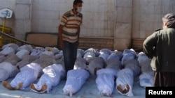 Arxiv foto: Suriyada kimyəvi silahla hücumdan həlak olan dinc sakinlərin cəsədləri dəfn üçün hazırlanır.