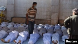Activists inspect the bodies of people they say were killed by nerve gas in the Ghouta region near Damascus on August 21.