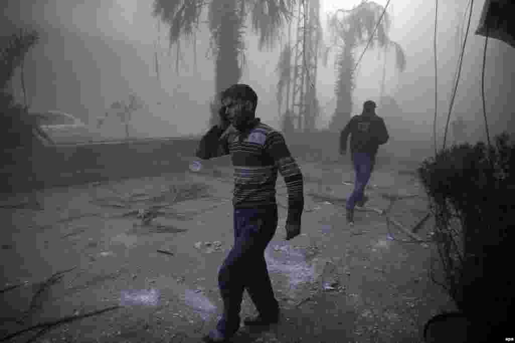 First Prize Stories in the Spot News Category was won by Syrian photographer Sameer Al-Doumy for his dramatic images of the the aftermath of air strikes in Syria. This photo from the series shows a wounded man walking out of a dust cloud following reported air strikes in the town of Hamouria, Syria. (December 9, 2015)