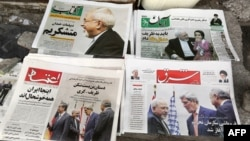 Iranian newspapers headlining the deal made in November between major powers and Iran over that country's disputed nuclear deal are displayed on the ground outside a kiosk in Tehran on November 25.