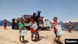 Покинувшие Мосул семьи в лагере в городе Эрбиль. 16 июня 2014 года.